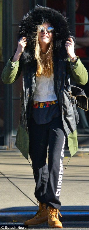 Hood up!: Cara went fur first as she tried to protect herself from the chilly New York weather