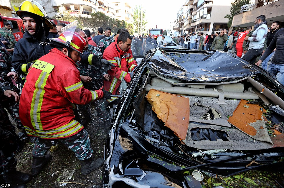 Recovery effort: Lebanese Red Cross workers pull a body from a car at the scene where two explosions have struck near the Iranian Embassy killing at least 23
