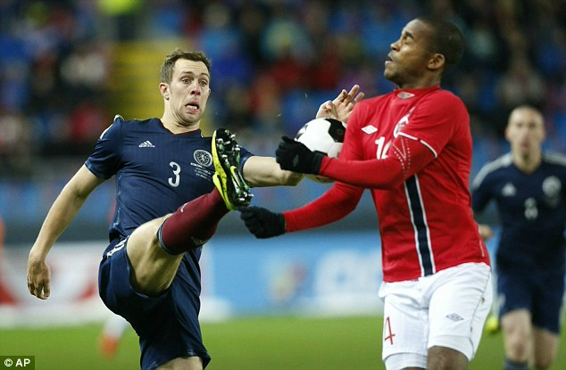 High boot: Scotland's Steven Whittaker challenges Ola Kamara