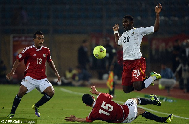 Chop: Egypt player Mohamed Naguib (bottom) vies for the ball with Ghanas Kwadwo Asamoah
