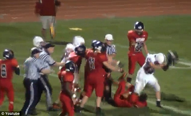 On-field altercation: Joey Cominsky (in white) can be seen swinging the helmet at a prostrate Josh Hartman