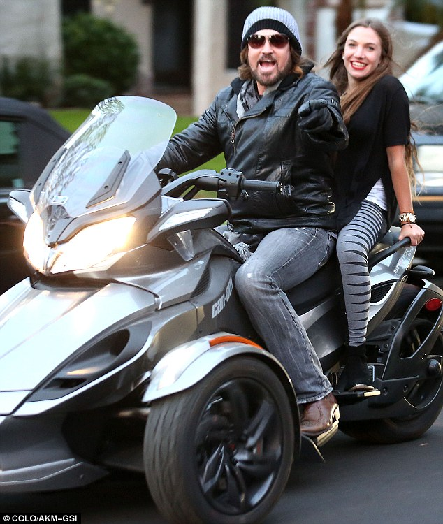 Lovely ride: Billy Ray Cyrus appeared to be having a ball riding with a female companion in Los Angeles on Friday