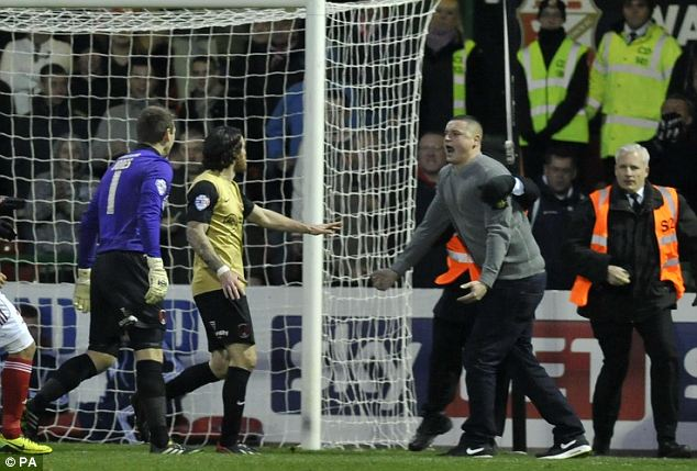 Outrage: Stewards grab the fan, who was later arrested 'on suspicion of affray', as he confronts players