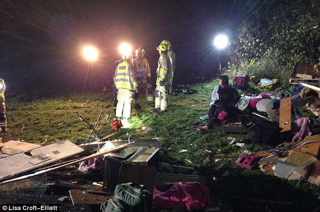 Clean-up: A woman can be seen sitting in the wreckage while the emergency services operation continues into the night