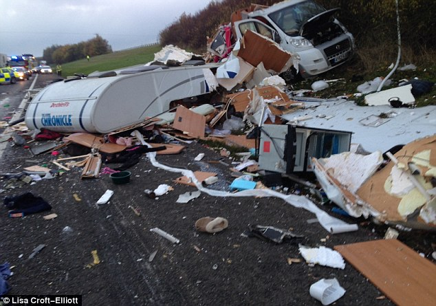 Smash: The remains of the motorhome, which had contained 12 dogs, can be seen here as police surround the crash site on the M40