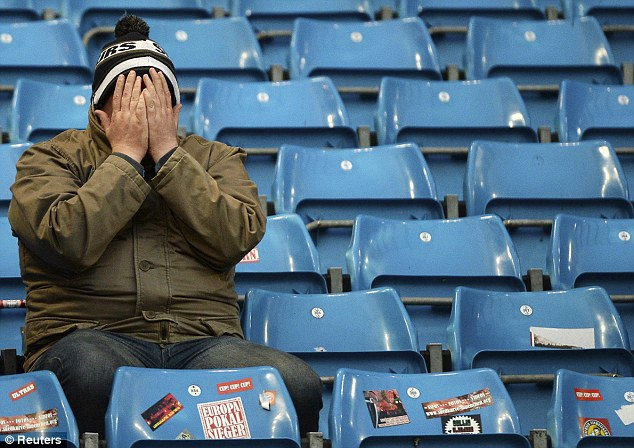 Tell me when it is over: A sole Tottenham fan with his head in his hands  following his side's poor display