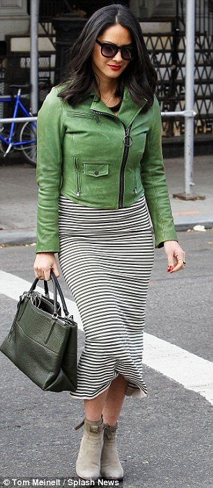 Shady lady: For her day out, the brunette beauty donned a gamete of green which included a dark olive striped dress and a bright grass green leather jacket