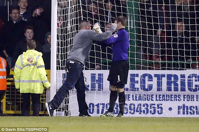 Thuggish: One 'fan' rushed on to the pitch and punched Leyton Orient keeper Jamie Jones several times