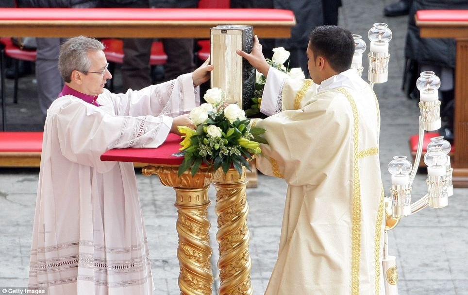 Reveal: A priest opens the relics, which were first discovered in 1939, during the mass