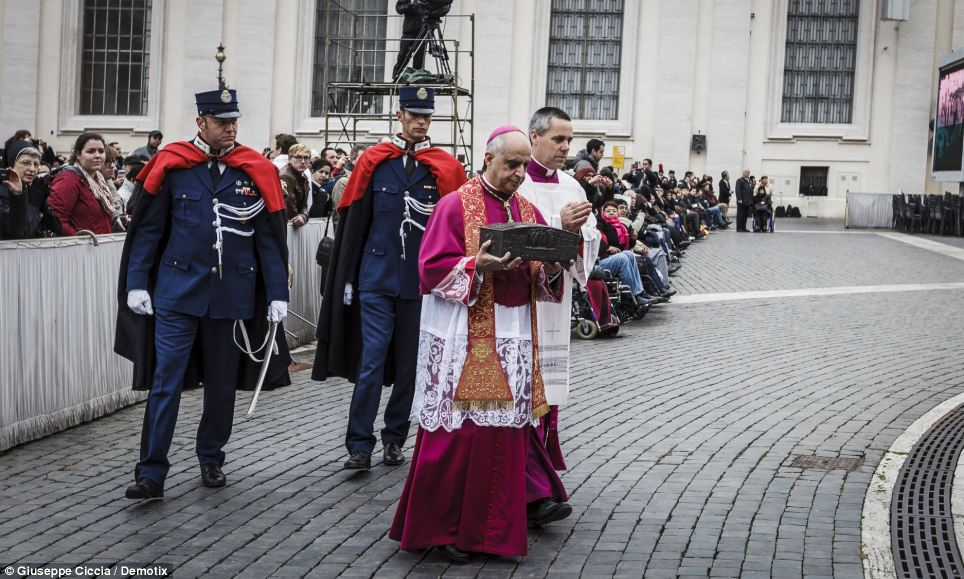 Debate: There is debate between the Vatican and some scholars over whether the relics - carried during a procession prior to the start of a Holy Mass, pictured - belong to the first pope