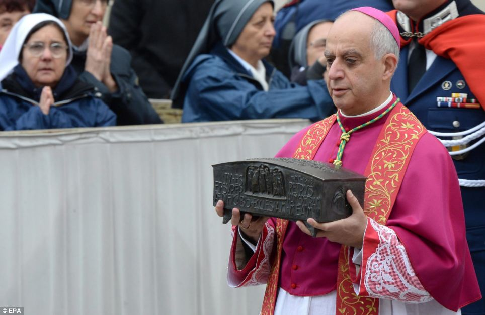First: Italian archbishop Rino Fisichella holds the box containing bone fragments, which are thought to belong to St Peter