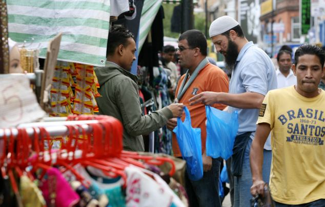 Segregated: Members of the Bangladeshi community in Whitechapel east London, the research shows that ethnic minority groups stick to diverse urban areas while the countryside remains overwhelmingly white