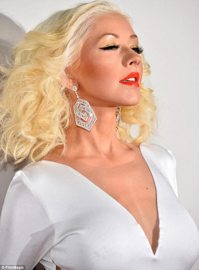 Golden girl: Christina's wore shimmery gold eyeshadow, black eyeliner and red lipstick for makeup