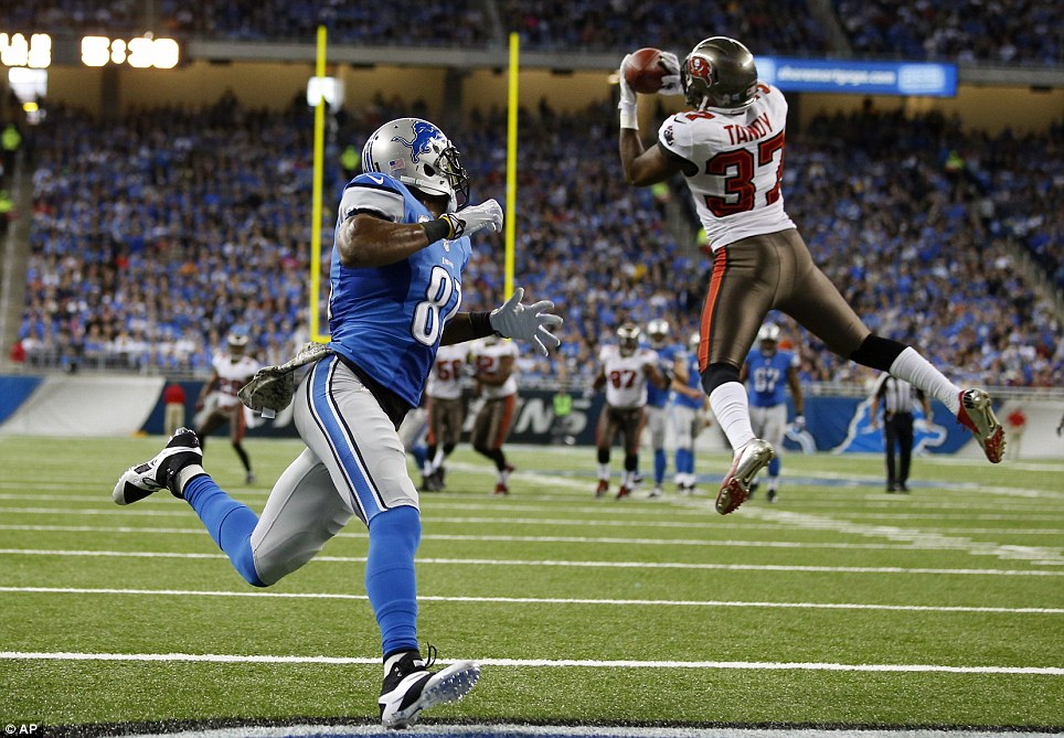 Tampa Bay Buccaneers free safety Keith Tandy intercepts a pass intended for Detroit Lions wide receiver Calvin Johnson during their NFL clash in Detroit
