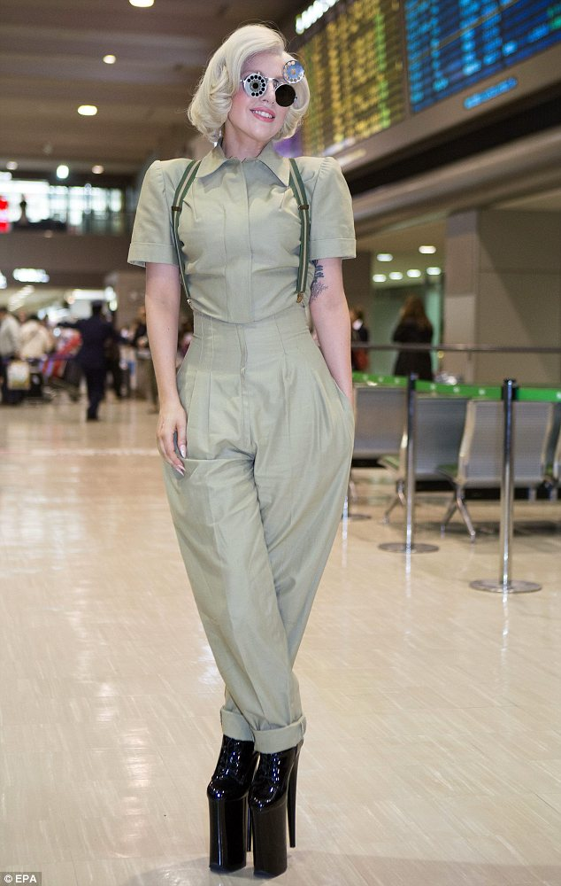 Dressing down: Lady Gaga a shirt and trousers ensemble complete with braces and killer heels at Narita International Airport in Tokyo