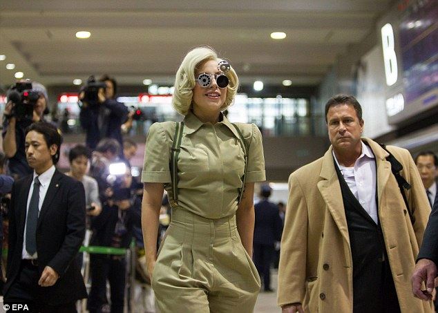 Centre of attention: All eyes are on Gaga as she makes her way across Narita International Airport