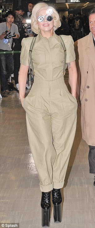 Careful! Gaga wore a tan boiler suit with incredibly high heels for her arrival