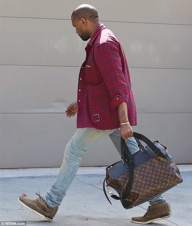 Luxury: Kanye carrying a Louis Vuitton bag in Los Angeles last month