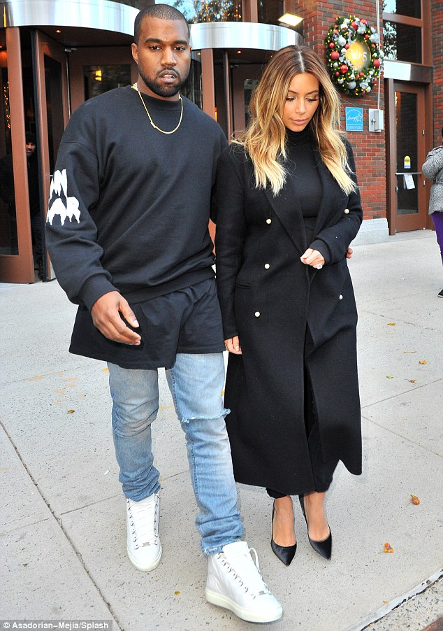 Loved-up: Kanye, who popped the question to his long-term love last month, put a protective arm around Kim as they headed out for the day