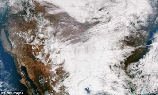 Taking over: An image released by NASA shows the large winter system moving across the United States that's combining with cold air from Canada, bringing snow and travel chaos to some areas