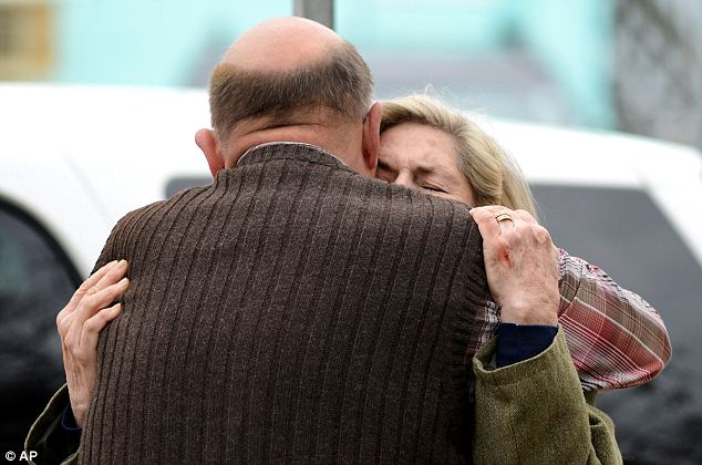 Devastated: Members of the congregation, Diane Savage and Bruce Young, hug in front St. Paul's By The Sea on Baltimore Avenue in Ocean City, Maryland, after the tragic news