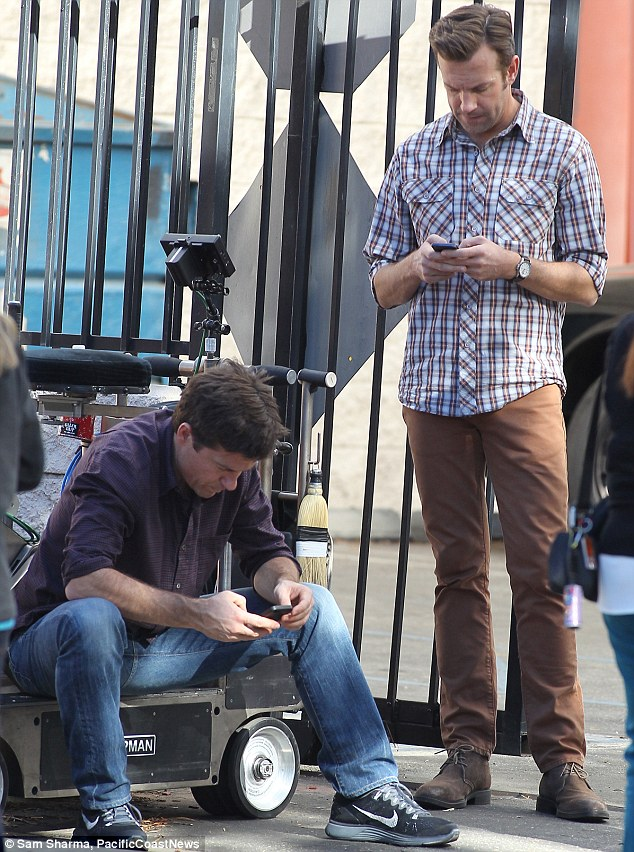 It beats talking to each other: Jason Bateman and Jason Sudeikis were engrossed in their phones on the set of Horrible Bosses 2 in Los Angeles on Wednesday