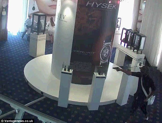 Brazen: The thief, a member of the Pink Panthers, seen bottom right of the picture, threatens staff with a handgun as he makes off with £88million of jewels from the Carlton Hotel in Cannes last July
