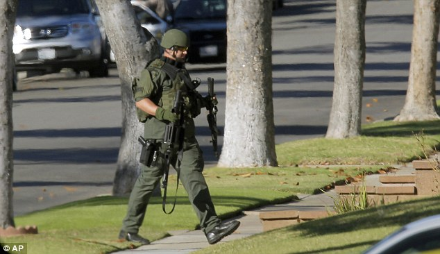 An Inglewood police officer moves into position outside a residence following reports of an active shooter