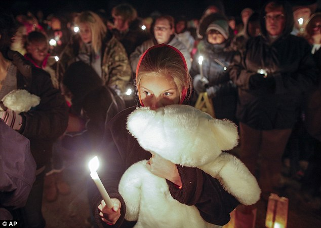 Support: Lexi Umbarger cuddles a teddy bear during a vigil for the family found murdered on Monday