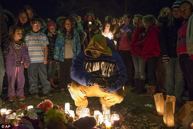 Tribute: Donald Betts, the father of Hollie, Jaxon and Averie, kneels at a makeshift memorial in Parsons on Wednesday