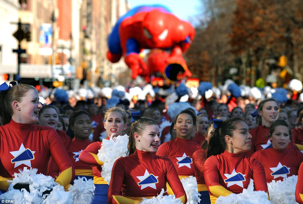 Spirit: Cheerleaders keep a smile on despite the cold as they march in the parade today