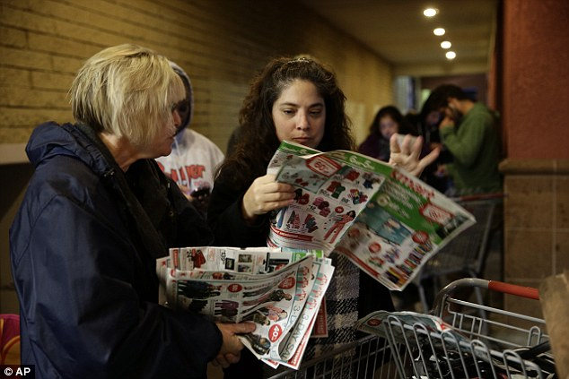 Waiting: Katie Stroh, left, and Gretchen Burkhardt look at catalogs while waiting outside a Kmart store on Thursday, Nov. 28, 2013, in Anaheim, California