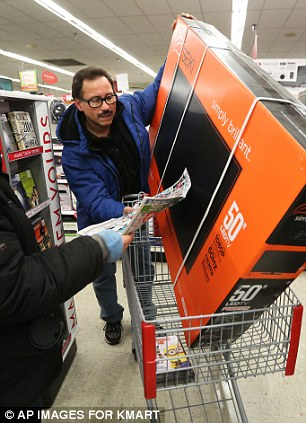 Barbie and televisions for Christmas: Stephanie Torres, of Chicago, stocks up on Barbie dolls during Kmart's Thanksgiving Day doorbuster sale at the Addison St. Store in Chicago whilr Luis Torres piles in a tv-set into his trolley