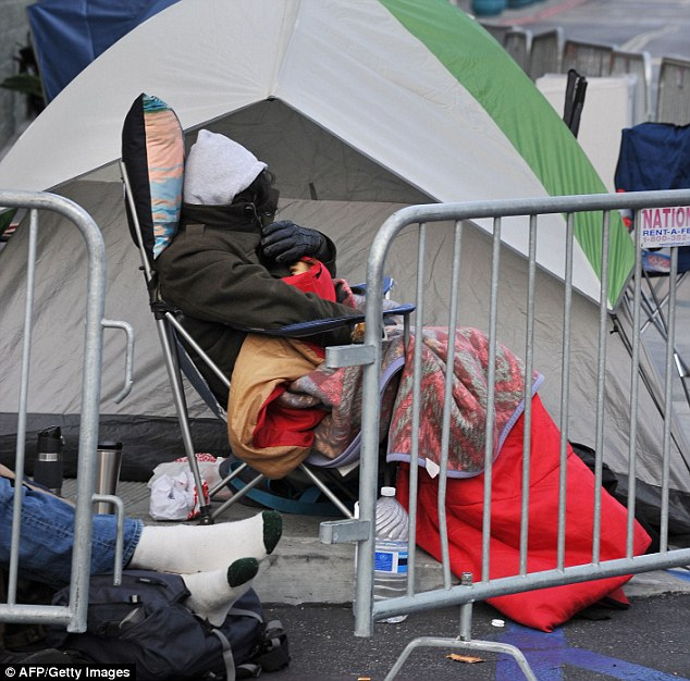 Dedication: A man tries to stay warm while waiting in line outside the Best Buy store in Burbank, California for the store to open on Thanksgiving Day, November 28, 2013