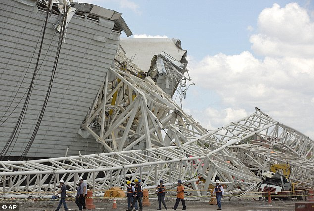 In mourning: Two workers were killed when a crane crashed into the stadium in Sao Paulo which is due to host the opening game of the 2014 World Cup in Brazil