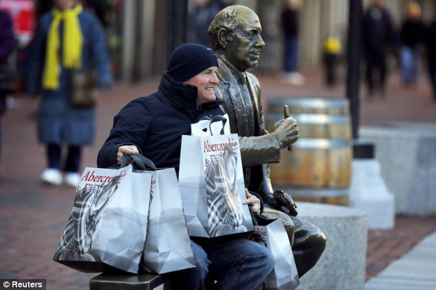 Happy customer: A man poses for a photograph with his shopping bags and a statue of hall of fame Boston Celtics coach Red Auerbach on Black Friday in Boston