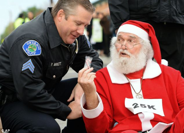 Arrest: In Ontario, Wal-Mart protester Karl Hilgert, dressed as Santa Claus, hands Ontario police department Sgt. Pat Birkett a candy cane as Hilgert is arrested for failure to disperse