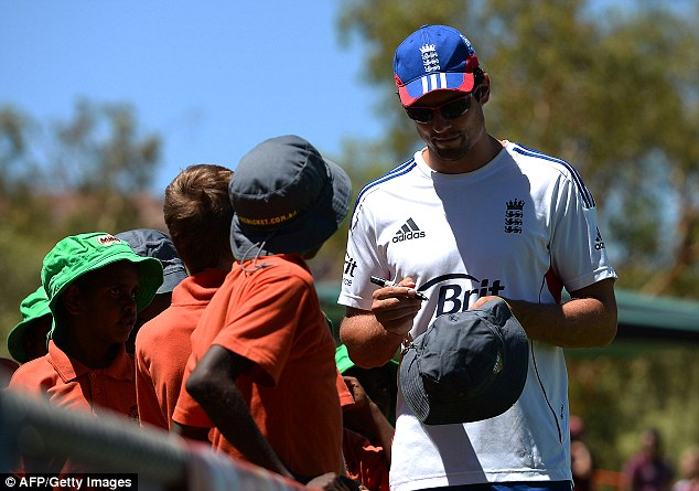 Sign of the times: England captain Cook is not playing but took time to pen autographs for young fans
