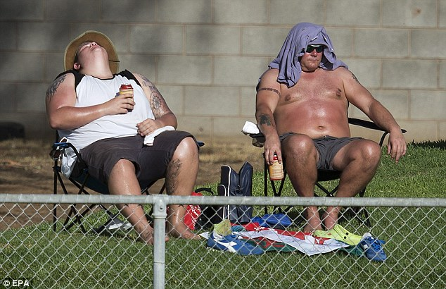 Tan time: Two spectators soak up the sunshine and enjoy a beer while watching the cricket
