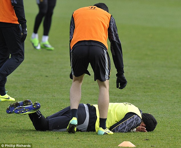 On your feet: Suarez is encouraged to get back up by one of his Liverpool team-mates