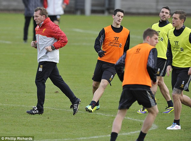 Running things: Rodgers joins in with the players as they jog