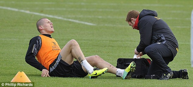 Help needed: The Liverpool defender waits for treatment as the physio delves into his medical bag