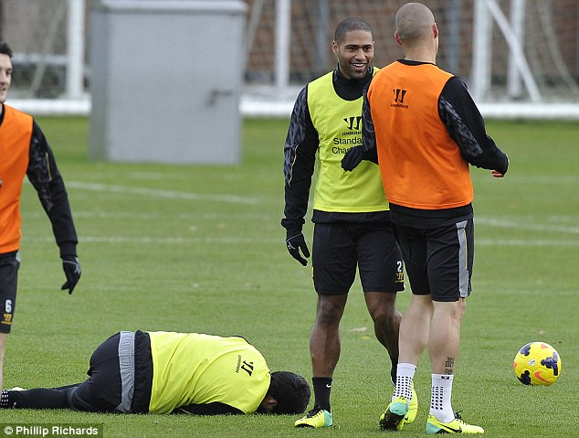 No sympathy: Skrtel (right) and Glen Johnson seem to be having a joke as Luis Suarez (left) lies on the ground