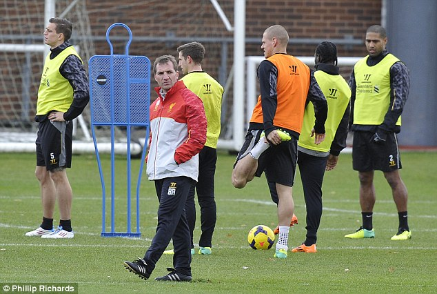 Stretching the point: Skrtel does some exercises (third right) as manager Brendan Rogers has a stroll