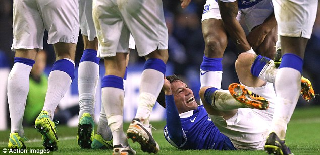 Falling at your feet: Everton players crowd an overjoyed Oviedo after the Costa Rican made it 3-0