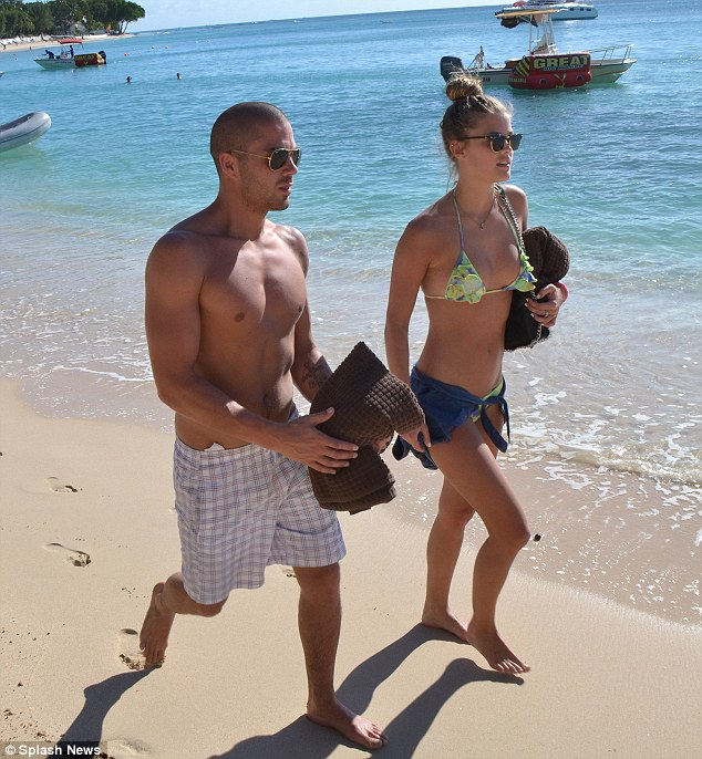 Prepared: The couple clutched brown towels as they sashayed across the beach
