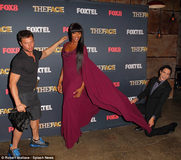 Fashion royalty: Zac straightened out the star's train as she posed for photographers