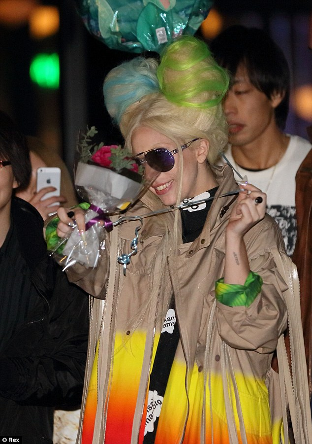 Romance isn't dead: Gaga smelt the roses she was handed by one star-struck fan in Japan