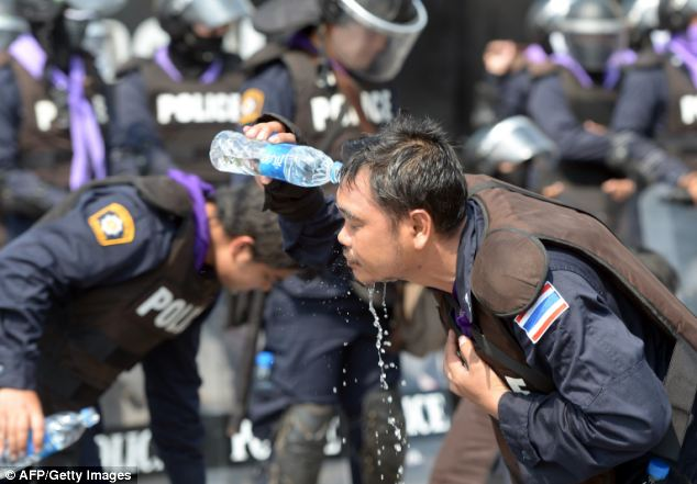 Break: Riot police take a break to clean their faces after launching a gas assault on the violent demonstrators