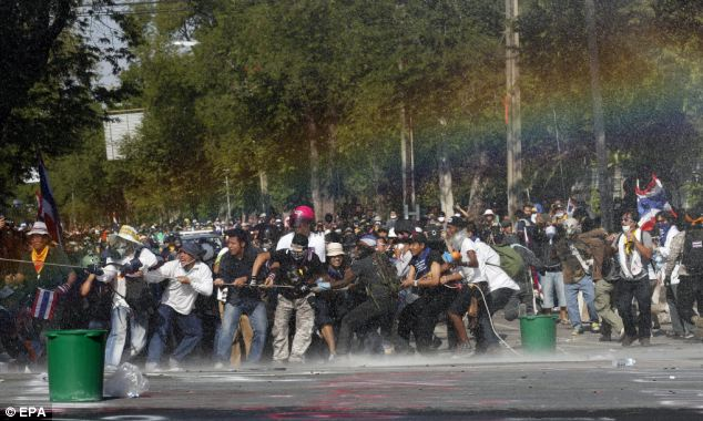 Effect: A rainbow forms in water cannon spray as protestors attempt to remove police barricades in the capital